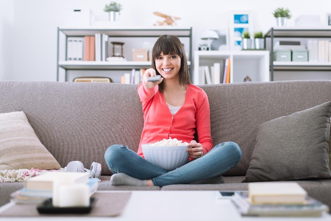 Woman sitting on sofa and holding remote control